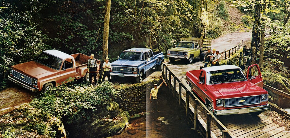 A photo from the original 1973 Chevy truck brochure showing four C/K Series pickups clustered together on a dirt road and a wooden bridge next to a steep, tree-covered hillside.