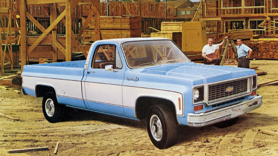 A photo from the original 1973 Chevy truck brochure showing a blue and white C/K Series pickup in a lumber yard. Two men stand behind the truck.