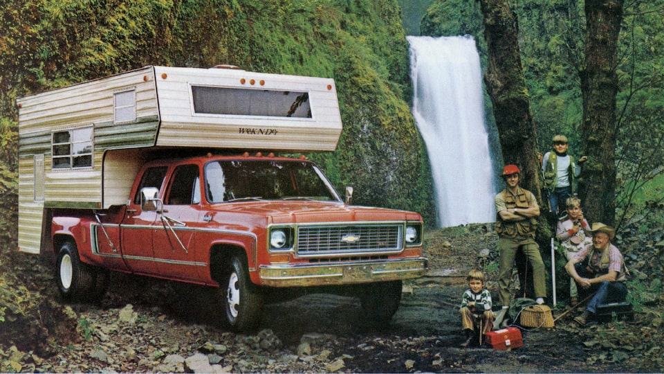A photo from the original 1973 Chevy truck brochure showing a red C/K Series pickup with a bed camper, sitting in a wooded area near a waterfall. A man and four boys of different ages sit and stand next to the truck.