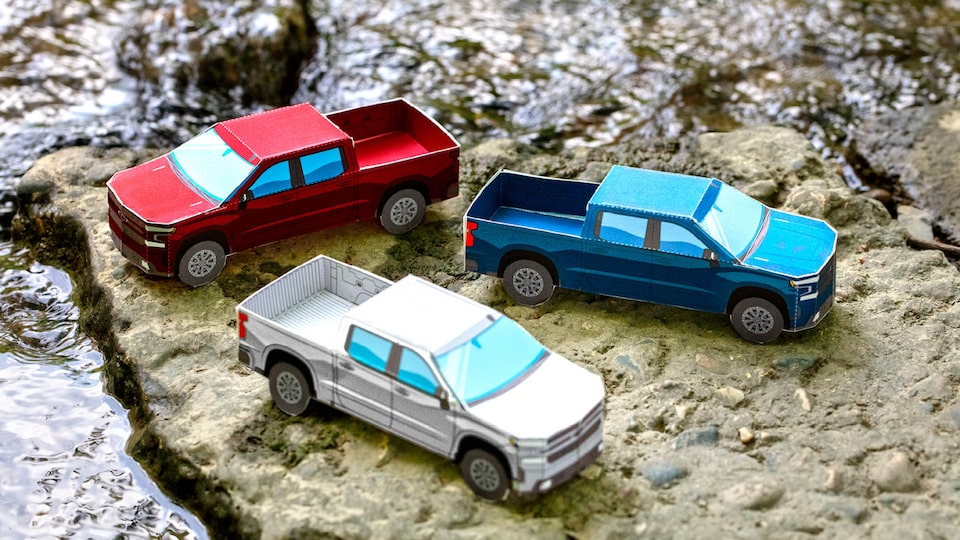 Miniature paper models of the 2020 Silverado RST Diesel in Cajun Red, Silver Ice Metallic, and Northsky Blue Metallic sitting on bare, rocky ground.
