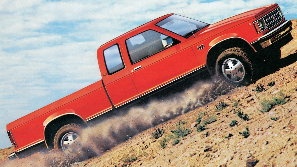 A red 1983 Chevy S-10 pickup drives through a flat desert area in an image from the 1983 brochure.