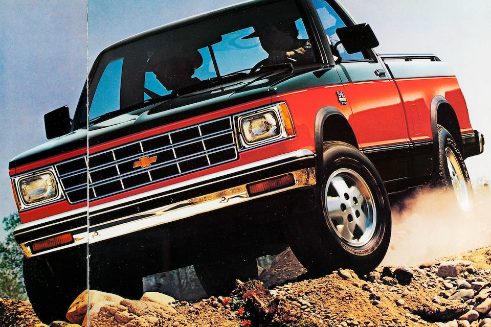 A two-tone red and black 1983 Chevy S-10 pickup drives over rough ground in a photo from the 1983 brochure.