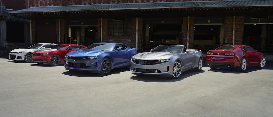 A group of five Camaros parked at a loading dock: White, red and blue coupes and a silver convertible.