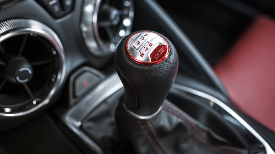 A Camaro interior accented with a red shift knob, red stitching and red seat surface.
