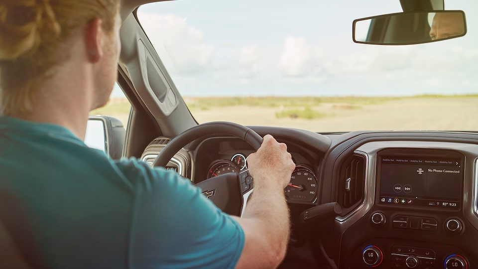 Seen from the backseat of a Chevy Silverado, a man in a green t-shirt is driving through a coastal area.