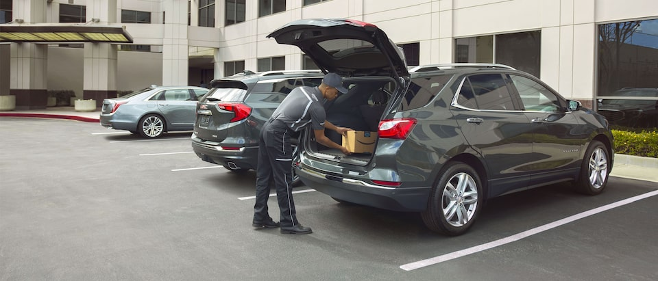 A delivery man places an Amazon package inside a Chevrolet Equinox.