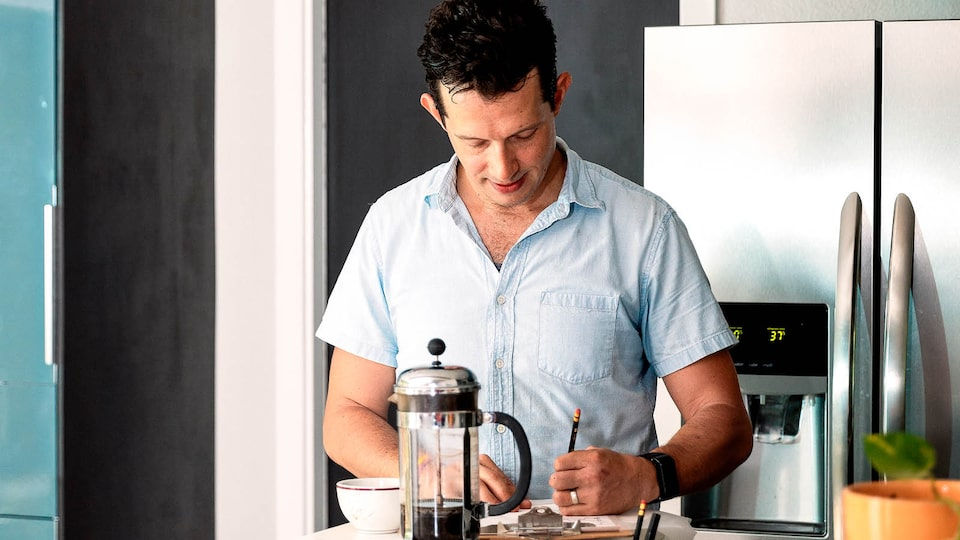 Jon Hagar writes notes on the counter in his kitchen, with a coffee press and cup near him and the refrigerator behind him.