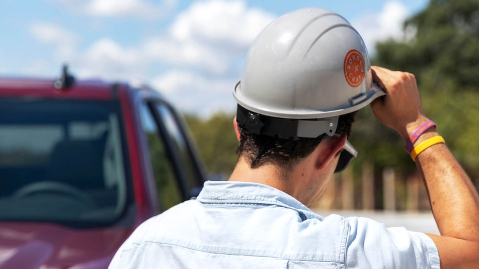 A rear shot of Jon Hagar as he removes his construction hard hat. Part of the cabin of the Chevrolet Silverado is visible in the background.