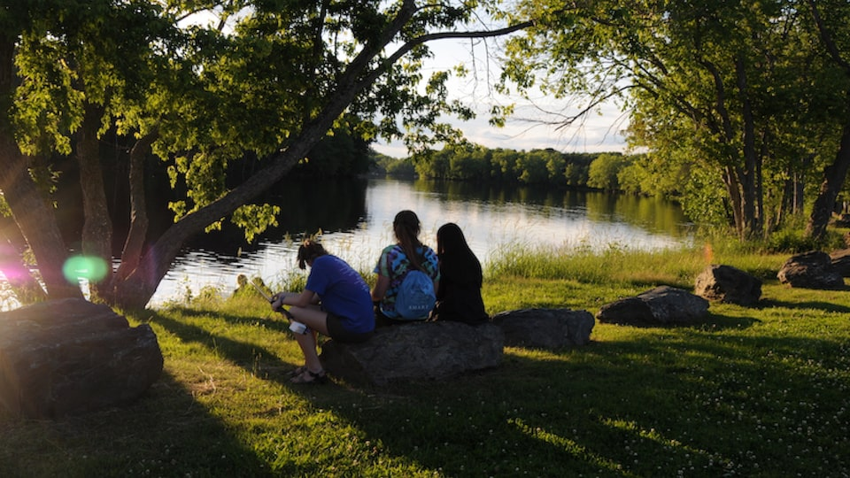 Students from the University of Maine Stormwater Management and Research Team sit near a pond.