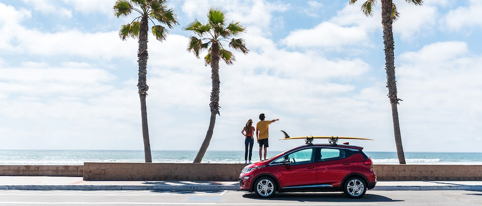 A red Chevrolet Bolt EV with a surfboard strapped to a roof rack sits on a road in front of three palm trees and the beach and ocean beyond the trees. Two people stand on a short wall behind the Bolt EV pointing out at the water.