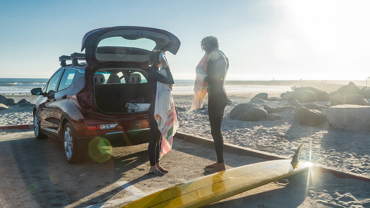 Two people in wetsuits walk from a park- ing lot out onto an ocean beach carrying a  surfboard. A red Chevrolet Bolt EV sits in  the parking lot