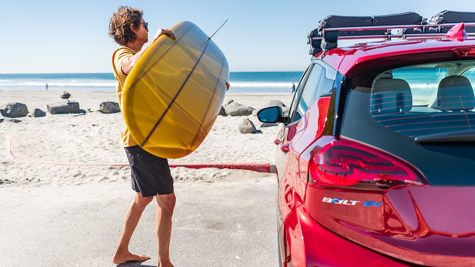 A man holding a surfboard prepares to load it onto the roof rack on a red Chevrolet Bolt EV. The beach is in the background.