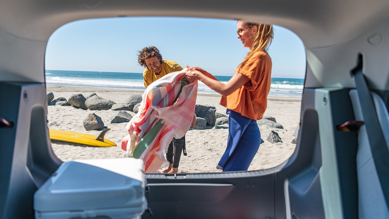 With a viewpoint from inside a Bolt EV looking out the raised hatch in back, a woman and a man unload surfing gear onto a beach. The ocean is in the background.
