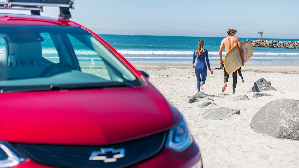 A woman and a man holding a surfboad walk across the beach toward the ocean. A red Chevrolet Bolt EV is in the foreground.