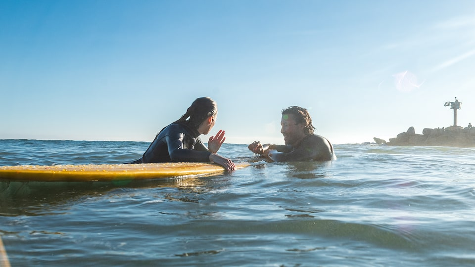 A woman and man float in the water holding on to a surfboard.