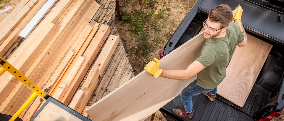 Seen from above, a man in work clothes and gloves moves sheets of plywood from the bed of a black Chevy Silverado pickup truck onto a nearby stack of lumber.