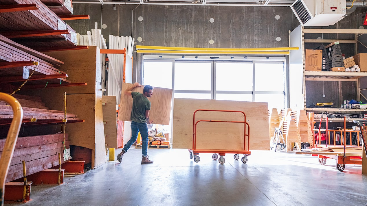 Inside a lumber warehouse, a man in work clothes moves sheets of plywood onto a cart.