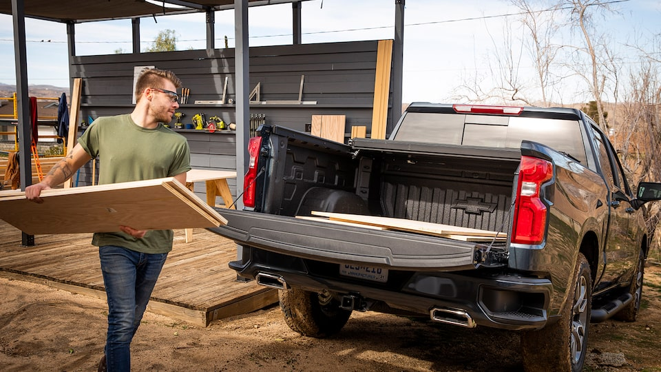 A man in work clothes and safety glasses loads sheets of plywood into the open bed of a black Chevy Silverado pickup.