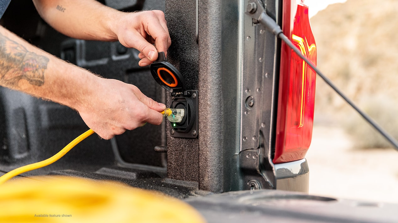 A man's hands are seen plugging a yellow extension cord into the outlet in the back of the bed of a black Chevy Silverado pickup.