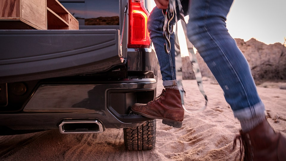 The lower part of a man's legs and his boots are seen as he steps into the corner step in the back bumper of a black Chevy Silverado pickup.