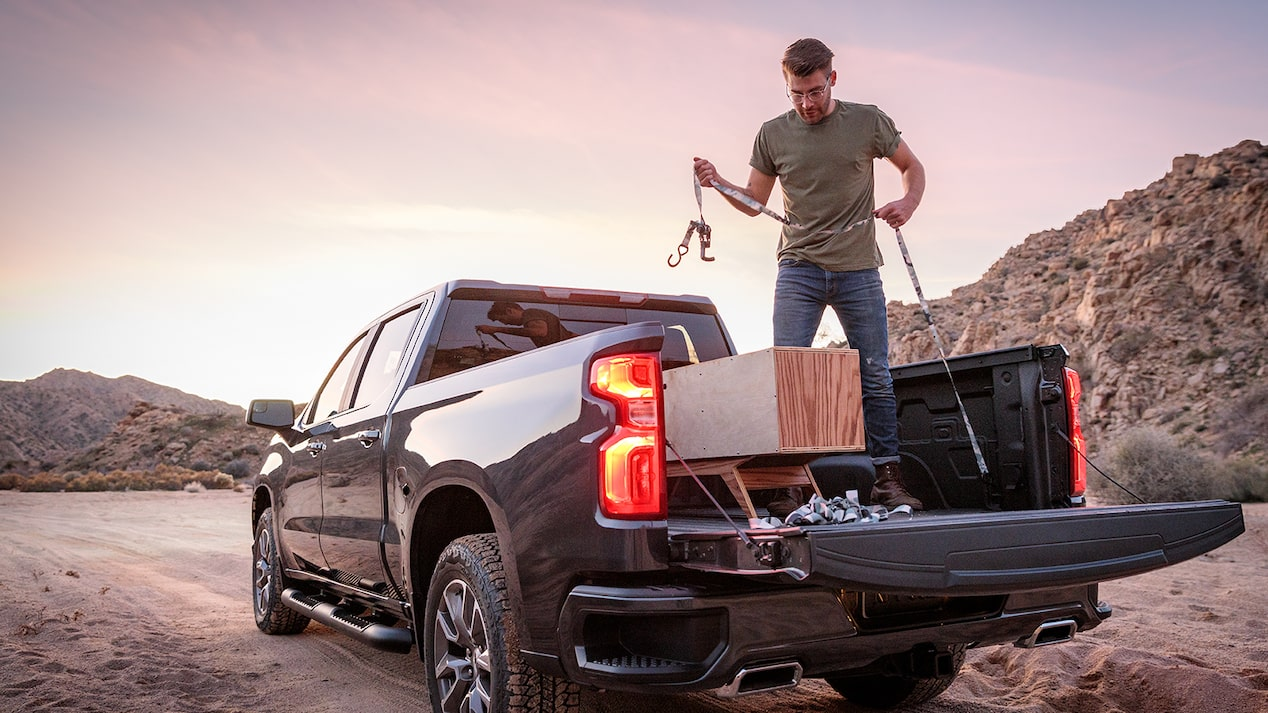 A man in work clothes stands in the open bed of a black Chevy Silverado pickup. He is strapping down some lumber in the bed.