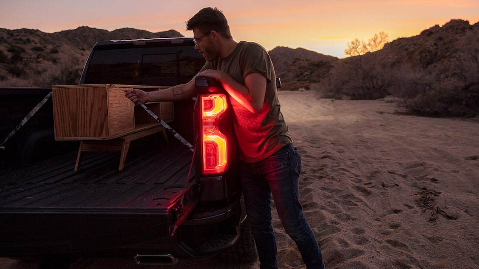 A man in work clothes kneels in the open bed of a black Chevy Silverado pickup. He is strapping down some lumber in the bed.