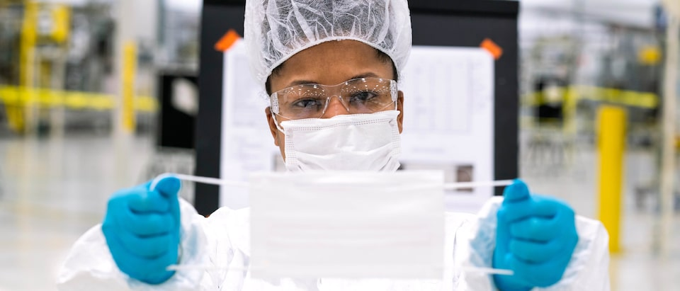 A person wearing a face mask, hair net, and gloves displays a face mask by holding it by the elastic on  both sides.