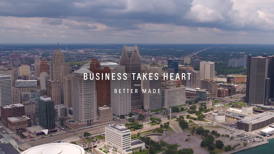 "A bird's-eye view of the Detroit skyline with the text ""Business Takes Heart - Better Made"" over  the image."