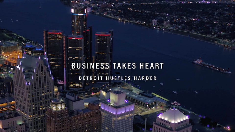 "A bird's-eye nighttime view of the Detroit skyline, with the text ""Business Takes Heart - Detroit Hustles Harder"" over the image."