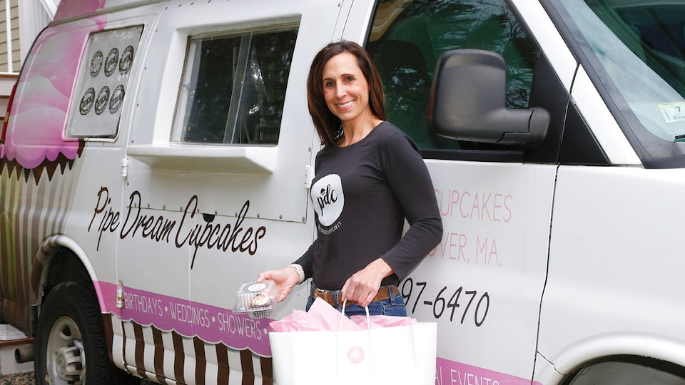 Nadine Levin stands next to her customized Chevy Express van outfitted with pink and black graphics for her Pipe Dream Cupcakes business.