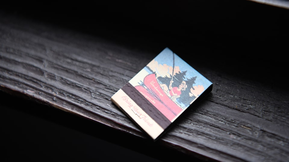 A matchbook with a tranquil scene of a canoe on a lake pictured on it sits on a wooden table.