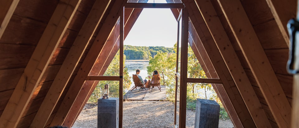 A man and woman sit at the edge of a lake, framed by the doorway of an a-frame cabin.