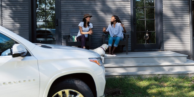 Two women sit and chat on the deck of a cabin, with a white Chevrolet Traverse in the foreground.
