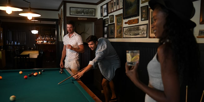 Two men play pool inside a camp lodge as a woman watches.