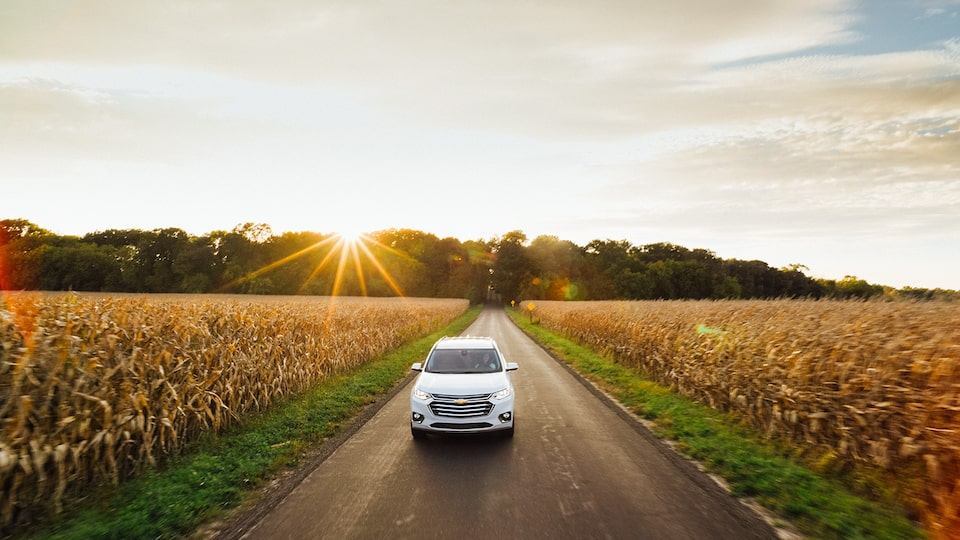 The front end of a Chevrolet Traverse as it drives down a contry road with the setting sun behind it.