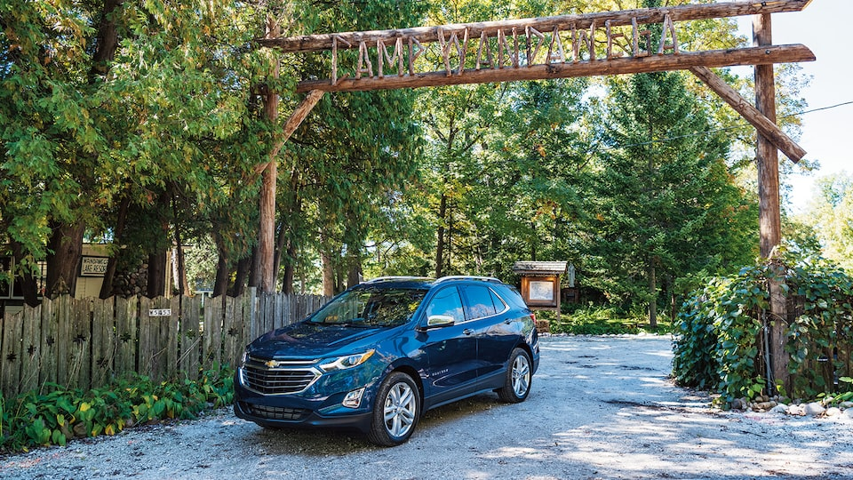 A Chevrolet Equinox drives under a rustic log gateway and sign for Camp Wandawega.