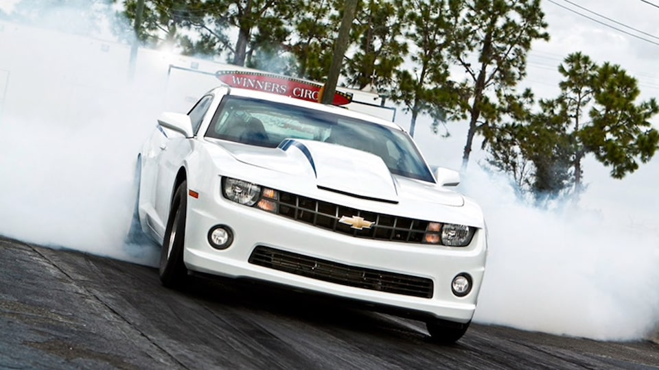 A white fifth-generation COPO Camaro warming up its tires on a drag strip with smoke coming from the tires.