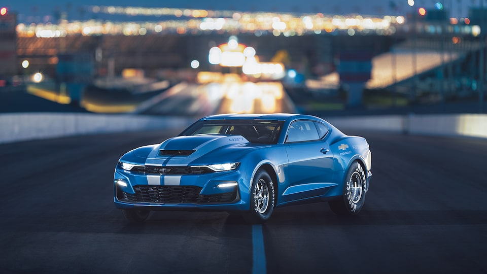 A 427-cubic-inch V8-powered blue COPO Camaro sitting on a drag strip with lights in the background.