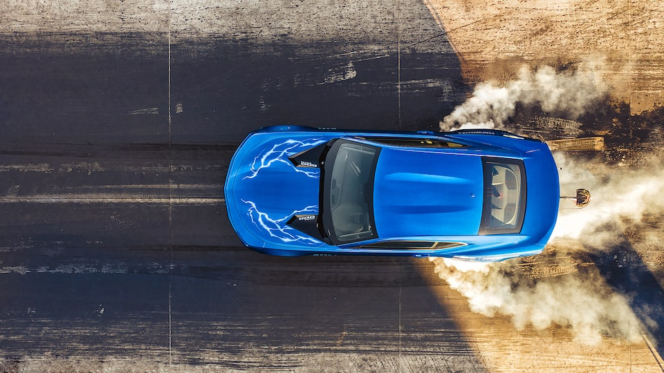 Seen from above, a blue electric drag racing eCOPO Camaro Concept smokes its tires on the track.