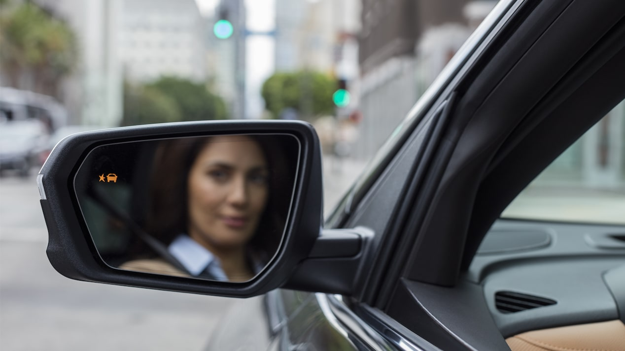 Close-up photo of a woman's reflection in the driver's side mirror of an Equinox.