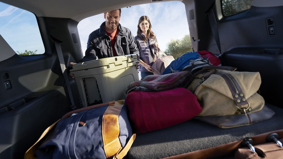 A man and woman unloading camping gear from the rear of a Traverse.