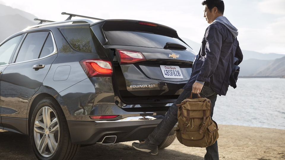 A man holding a bag opens the Equinox hands-free liftgate.