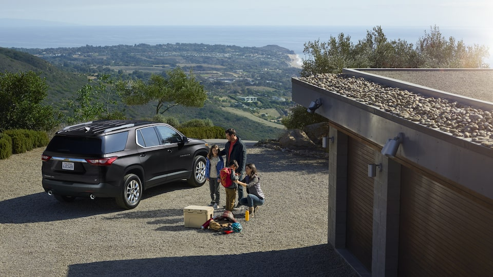 A family of four and their luggage stands outside of a Traverse.
