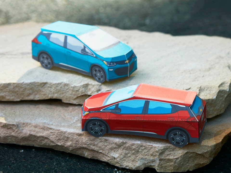 Miniature paper models of the Bolt EV in Cajun Red and Oasis Blue sit on a stack of flat rocks.