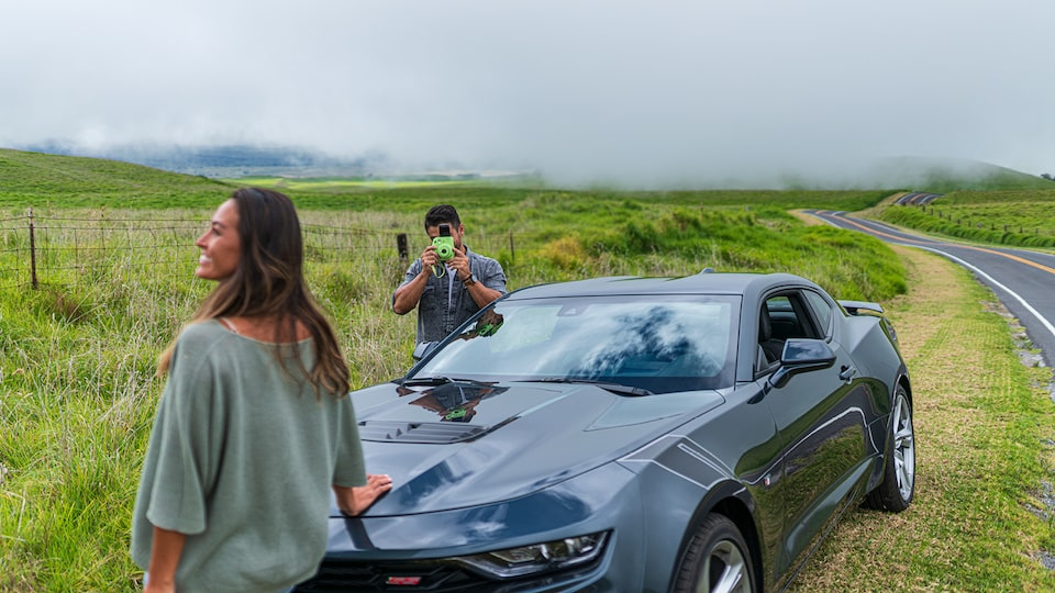 A man uses a Polaroid camera to take a picture of a women standing near the front of a 2020 Camaro SS.