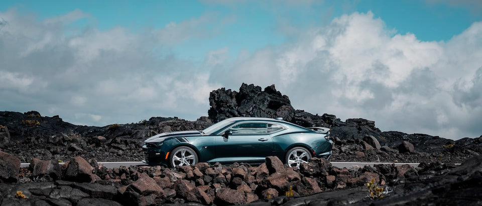 Side view of a 2020 Camaro SS surrounded by a rocky terrain.