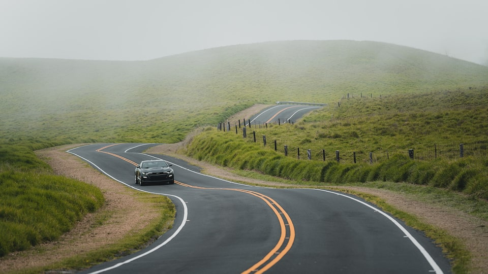 A 2020 Camaro SS drives on a winding and hilly two-lane road.
