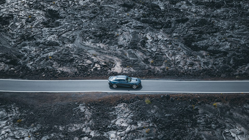A 2020 Camaro SS parked on a narrow roadway surrounded by black lava rock.