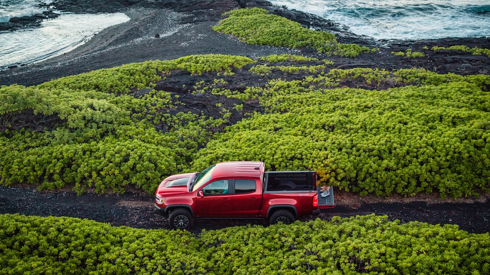 A side view of a red Chevrolet Colorado ZR2 stopped on a narrow road with greenery on either side.