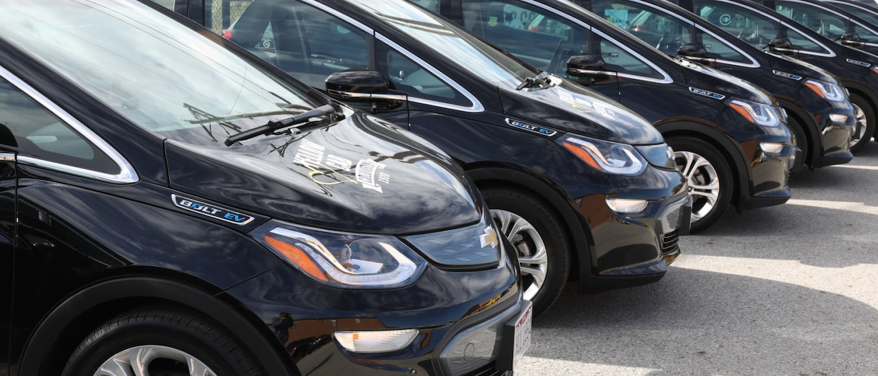 Several black Chevrolet Bolt EVs that are part of the Yellow Cab of Columbus fleet are parked in a row.